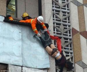 """Una foto drammatica che mostra i soccorritori impegnati a """"issare"""" la donna sul balcone (Quirky China News, come pubblicata dal Daily Mail)"""