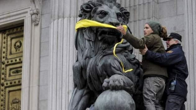 Un'attivista di Greenpeace ha imbavagliato la scultura di un leone a guardia del Parlamento spagnolo