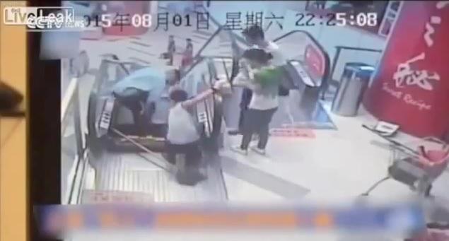 L'addetto delle pulizie incastrato nell'apertura delle scale mobili (screenshot da video Youtube)