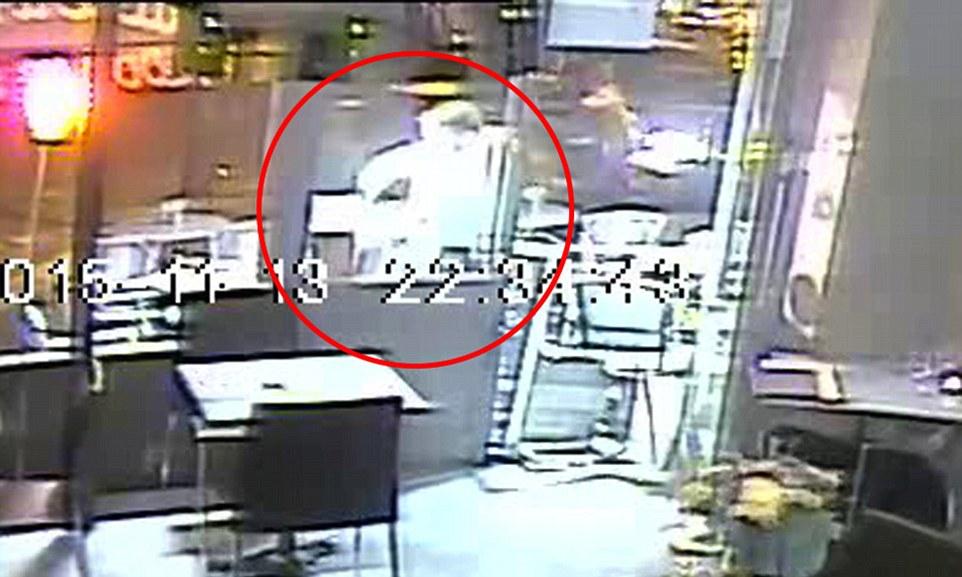 Il terrorista sta puntando l'arma contro la testa di una delle due ragazze accovacciate sotto un tavolo fuori dal ristorante (www.dailymail.co.uk)